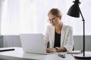 Geschäftsfrau prüft im Computer einen Unternehmenskauf