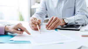 Geschäftsleute deuten auf einen Zettel mit Kugelschreiber