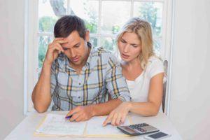 Junges Paar nachdenklich beim Tisch, schauen Rechnungen an