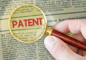 Lupe zeigt das Wort Patent in einer Zeitung