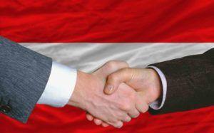 Unternehmer-Handschlag vor Österreich-Fahne