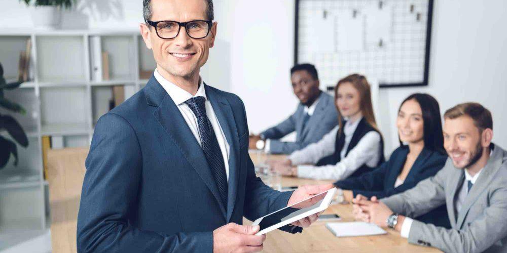 Geschäftsmann steht vor Mitarbeiter