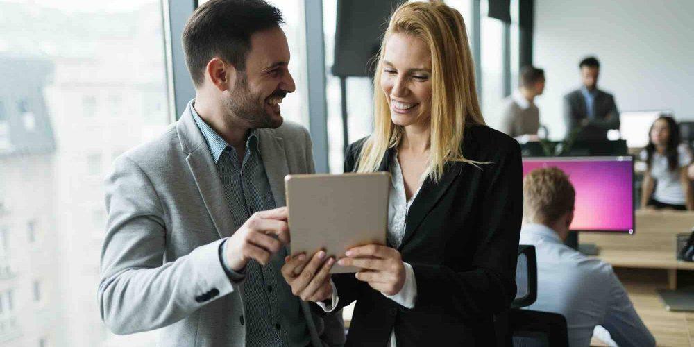 Geschäftspartner informieren sich am iPad wegen Umgründungssteuergesetz