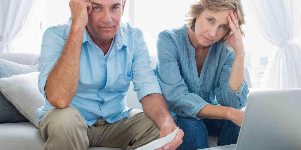 besorgtes Paar sitzt mit unbezahlten Rechnungen am Tisch